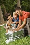 Family giving dog a bath. Royalty Free Stock Image