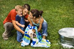 Family giving dog a bath. Royalty Free Stock Photo