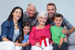 Family giving a gift to grandmother. Portrait of family giving a gift to grandmother, sitting on sofa in living room stock photo