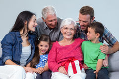 Family giving a gift to grandmother. Sitting on sofa in living room stock images