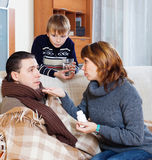 Family giving pills to diseased man Royalty Free Stock Images