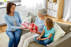 Family giving present and flowers to grandmother royalty free stock photos