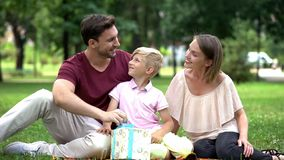 Family giving surprise gift to dad at fathers day or celebrating his birthday stock photo