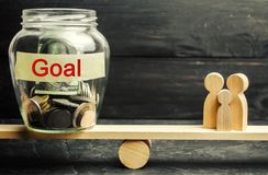 Family and glass jar with the inscription Goal. The concept of achieving family goals. The accumulation of money for the execution. Of targets. Achievement and royalty free stock image