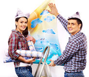 Family glues wallpaper at home. Stock Photo