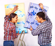 Family glues wallpaper at home. Royalty Free Stock Image