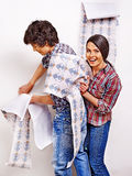 Family glues wallpaper at home. Royalty Free Stock Photo