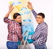 Family glues wallpaper at home. Royalty Free Stock Photography