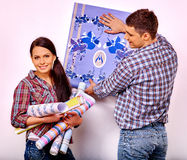 Family glues wallpaper at home Royalty Free Stock Image