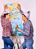 Family glues wallpaper at home Stock Photo