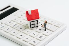 Family goals, building future with house cost calculation, mortgage and home loan or real estate concept, miniature couple figure. With small house on white royalty free stock photography