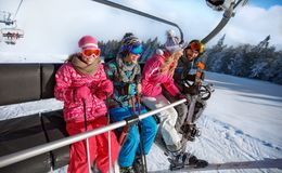 Family going on ski terrain with ski lift Royalty Free Stock Images