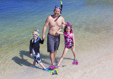 Family going Snorkeling at the Beach on vacation Stock Photo