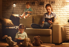 Family before going to bed mother and children read books and pl. Ay around the lamp in the evening stock image