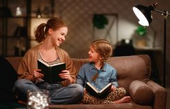 Family before going to bed mother reads to her child daughter book near a lamp in evening stock photo