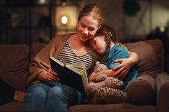 Family before going to bed mother reads to her child daughter book near a lamp in evening royalty free stock images