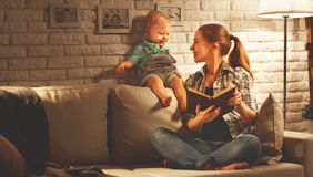 Family before going to bed mother reads to her baby son book nea. Family before going to bed mother reads to her baby son  book near a lamp in the evening Royalty Free Stock Photography