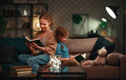 Family before going to bed mother reads to her child daughter book near a lamp in evening. Family before going to bed mother reads to her child daughter book stock image