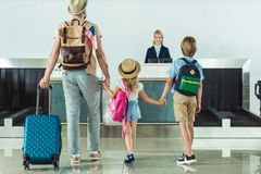 Family going to check in desk. Back view of family with backpacks going to check in desk at airport Stock Image