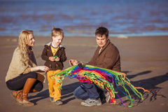 The family is going to fly a kite. The family is going to fly a rainbow-coloured kite at the seashore. Clothes: casual Royalty Free Stock Photos