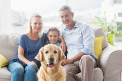 Family with Golden Retriever at home Stock Image