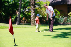 Family golf. Father and son playing golf. Focus on flag Stock Photography