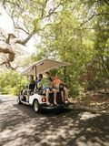 Family in golf cart. Caucasian family riding on golf cart on trail in North Carolina, USA Stock Image