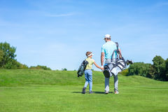 Family on golf course. Dad and son on golf course royalty free stock photos