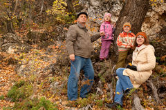 Family with grandfather in autumnal forest. Mother, daughter, son and grandfather in autumnal forest near the tree Royalty Free Stock Photography