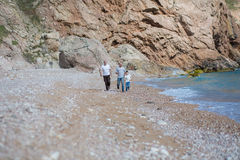 Family of grandfather father and son on a rocky beach on vacation enjoying time together Royalty Free Stock Photography
