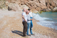 Family of grandfather father and son on a rocky beach on vacation enjoying time together stock image