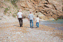 Family of grandfather father and son on a rocky beach on vacation enjoying time together Stock Photos