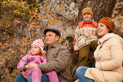 Family with grandfather sit on roots of trees. Mother, daughter, son and grandfather sit on roots of trees in autumnal forest Royalty Free Stock Image