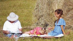 Family have a picnic in the meadow. Family with grandmother, mother and little daughter doing picnic outdoor with a melon in the meadow near the haystack stock video