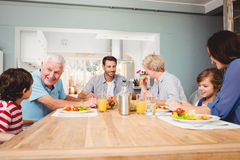 Family with grandparents discussing at dining table Stock Image