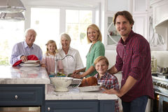 Family With Grandparents Make Roast Turkey Meal In Kitchen Stock Photos