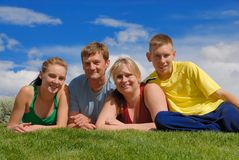 Family on grass. Family of four sit on grass Royalty Free Stock Images
