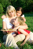 Family on grass. The young woman sits on a grass and reads the book to the children Royalty Free Stock Photography