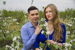 Family on green field. Beautiful caucasian pregnant couple in blooming garden Stock Photo
