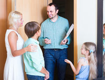 Family greeting guest at the door. Friendly family greeting guest at apartment doorway Royalty Free Stock Images