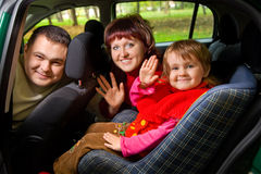 Family greeting to wave hands in car in park Royalty Free Stock Images