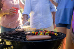 Family grilling patties, vegetables and sausages on the barbecue grill Royalty Free Stock Photo