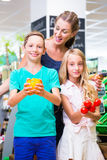 Family grocery shopping in corner shop Royalty Free Stock Images
