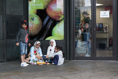 Family Group Eating Crossaints. 18th August 2015 - Family group sits on the ground eats outside a local shop displaying Best of British advert outside the busy royalty free stock photography