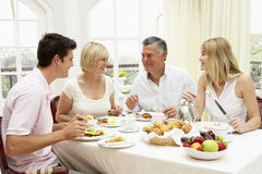 Family Group Enjoying Hotel Breakfast. Smiling at each other royalty free stock images
