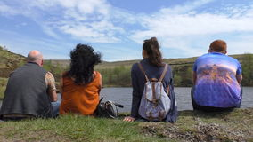 Family or group of four people sitting and enjoying day out stock footage