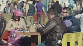 Family group sitting around table at summer festival food court. Caucasian family group sitting around table at summer festival food court reading brochures in stock footage