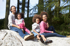 Family Group Sitting On Rock Together Royalty Free Stock Photo