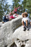 Family Group Sitting On Rock Together Royalty Free Stock Image
