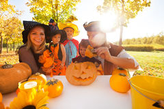 Family in Halloween costumes craft Jack-O'-Lantern Stock Photos